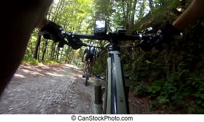 Mountainbiker riding down dirt road - Mountainbikers riding...