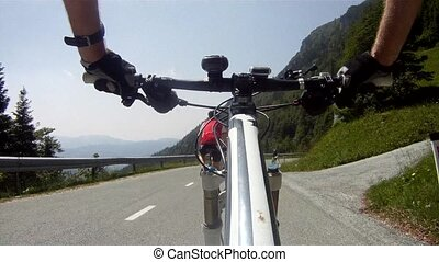 Mountainbiker riding down on road - Mountainbiker riding...