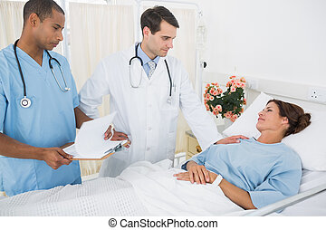 Doctors visiting patient in hospital - Doctor and surgeon...