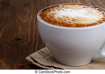 freshly made cup of cappuccino with abstract latte art, on...