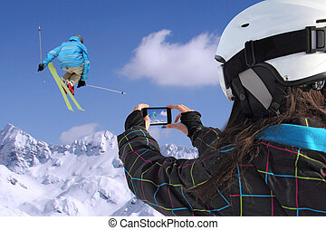 Mobile phone photographs of skiers jump - A young girl by...