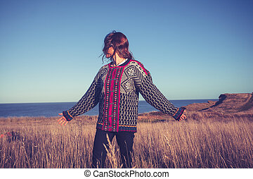 Young woman enjoying freedom in meadow by the sea