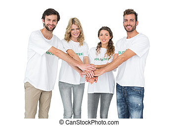 Group portrait of happy volunteers with hands together over...