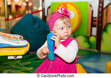 Happy child girl talking on the phone on playground The...