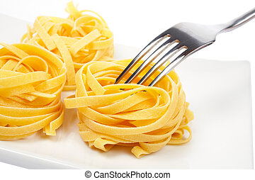 Uncooked pasta nests and fork - A uncooked pasta nests and...