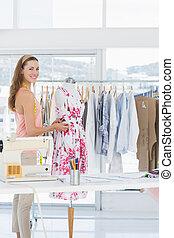 Female fashion designer working on floral dress at studio