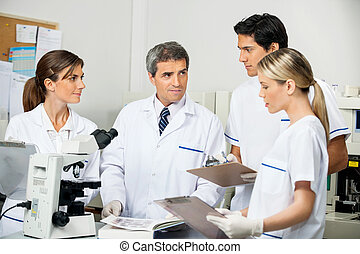 Scientist With Students Taking Notes In Laboratory - Mature...