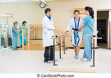 Physical Therapists Assisting Female Patient In Walking -...
