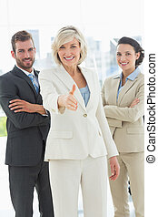 Confident businesswoman offering handshake with team in...