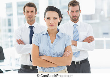 Confident business team with arms crossed in office -...