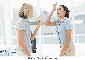Side view of two businesswomen fighting