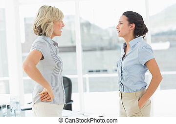 Side view of two businesswomen fighting in a bright office