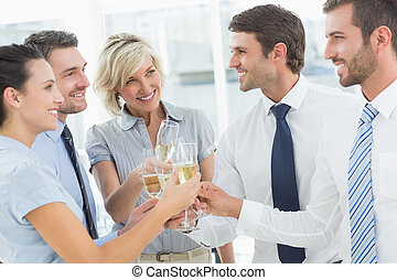 Business team toasting with champagne in office - Group of...