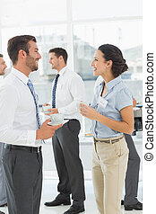 Colleagues in discussion with tea cups during break -...