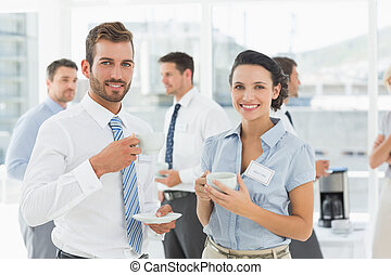 Business colleagues with tea cups during break - Portrait of...