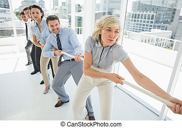 Group of business people pulling rope in office - Full...