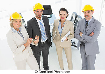 Confident architects with hard hats and blueprint in office...