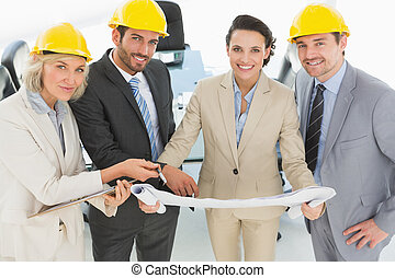 Well dressed architects with hard hats and blueprint -...