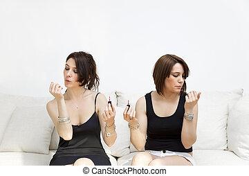 nail varnish - two young women blowing on nail varnish