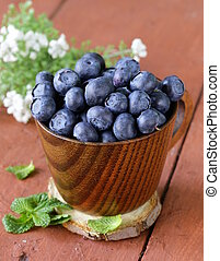 fresh organic ripe blueberries in a wooden bowl