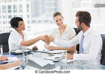 Executives shaking hands after a bu - Side view of...