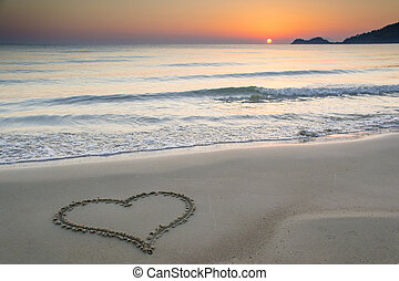 Love at sunrise - Heart shape drawn on a sandy beach at...