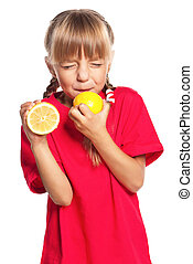 Little girl with lemon - Cute little girl eating fresh lemon...