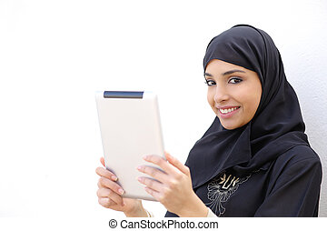 Arab woman holding a tablet and looking at camera on a white...