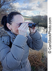 Woman looking through binoculars birdwatching on wetland