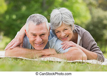 Smiling relaxed senior couple lying in park - Portrait of a...