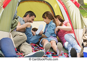 Family sitting in the tent at park