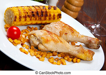 chicken thigh with a boundary of corn cob and salad
