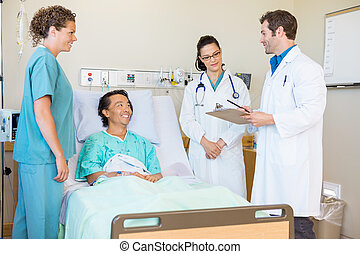 Young doctors discussing notes while happy patient and nurse...