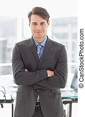 Handsome smiling businessman leaning on board room table in...
