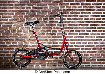 Mini red bicycle and red brick wall, vintage bike