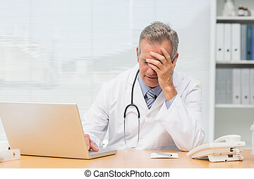 Stressed doctor sitting at his desk in his office at the...
