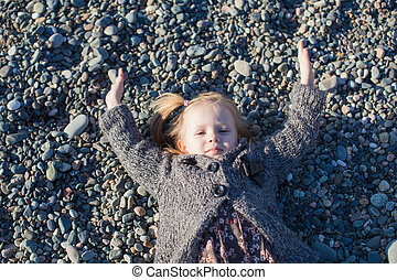 Adorable Little girl lying on the beach in a winter sunny day