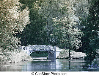 Trees and the bridge are reflected in the river, an infrared...