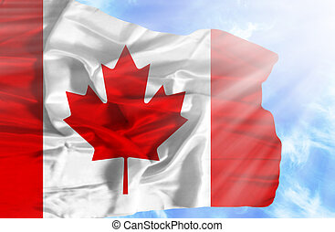 Canada waving flag against blue sky with sunrays