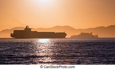 Alcatraz island penitentiary at sunset and merchant ship in...