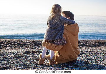 Young father and little girl at the beach on a sunny winter day