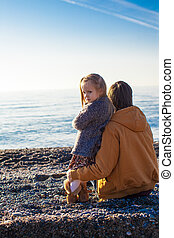 Back view of Young father and little girl at the beach on a sunny winter day