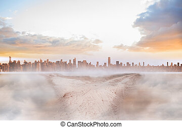 Dusty path in desert leading to city