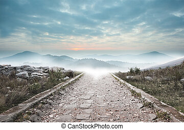 Stony path leading to misty mountain range