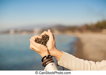 Woman hands holding small stones form heart shape background...