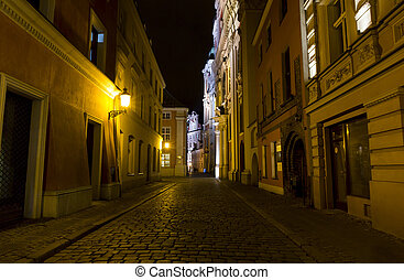 Night photo of a cobbled street lit with decorative lanterns...