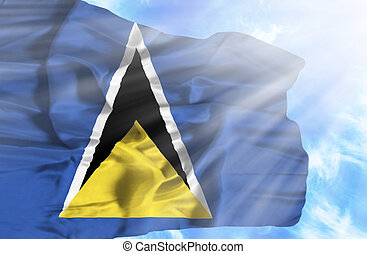 St Lucia waving flag against blue sky with sunrays