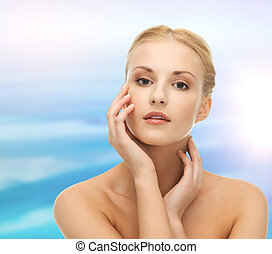 woman touching her face skin - health and beauty concept -...