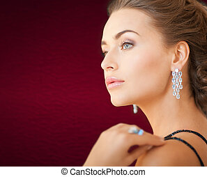woman with diamond earrings - jewelry and beauty concept -...