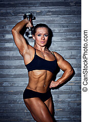Woman bodybuilder with dumbbell on wall background.